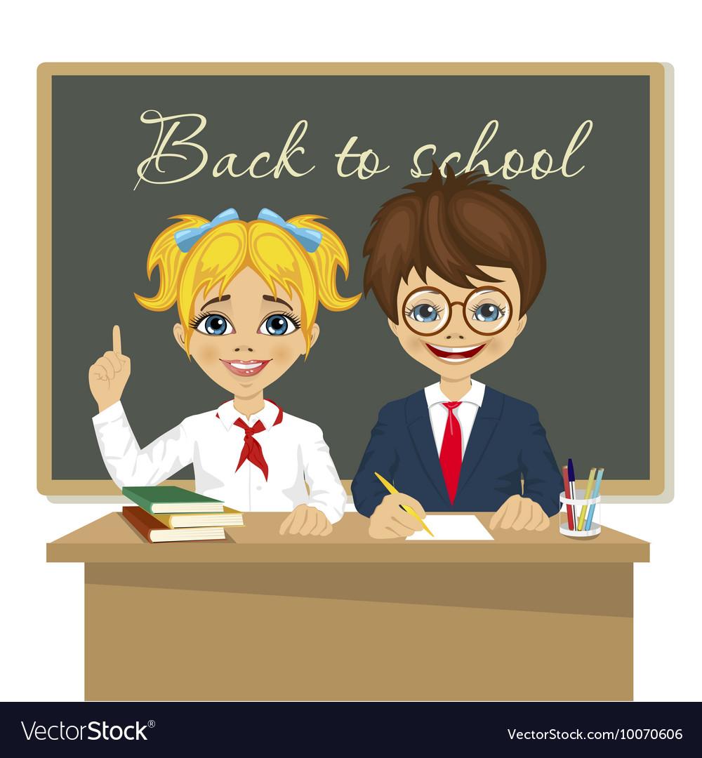 Schoolkids at desk sitting in front of blackboard