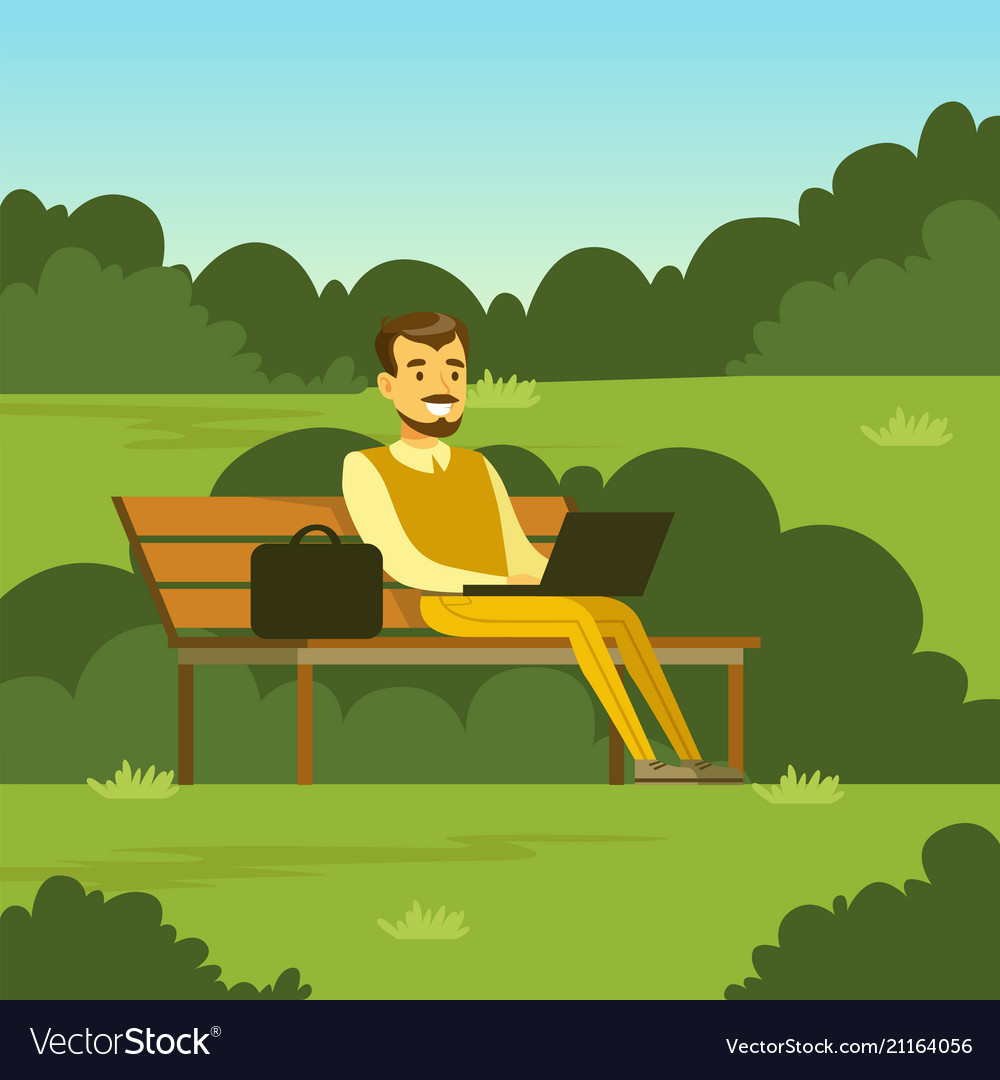 Young man sitting on the bench in the park using