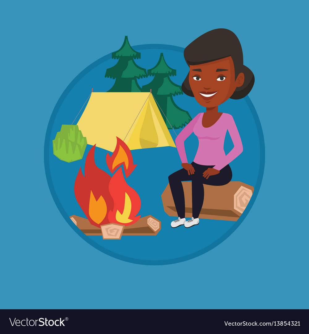 Woman sitting on log near campfire in the camping