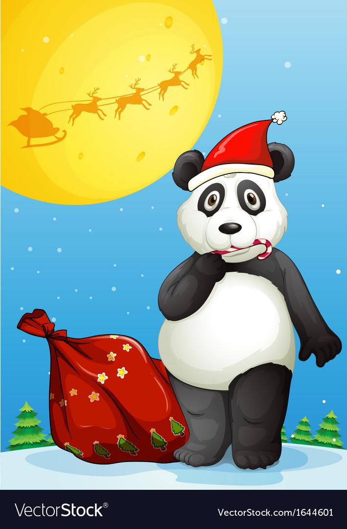 A panda wearing Santas hat while eating a cane