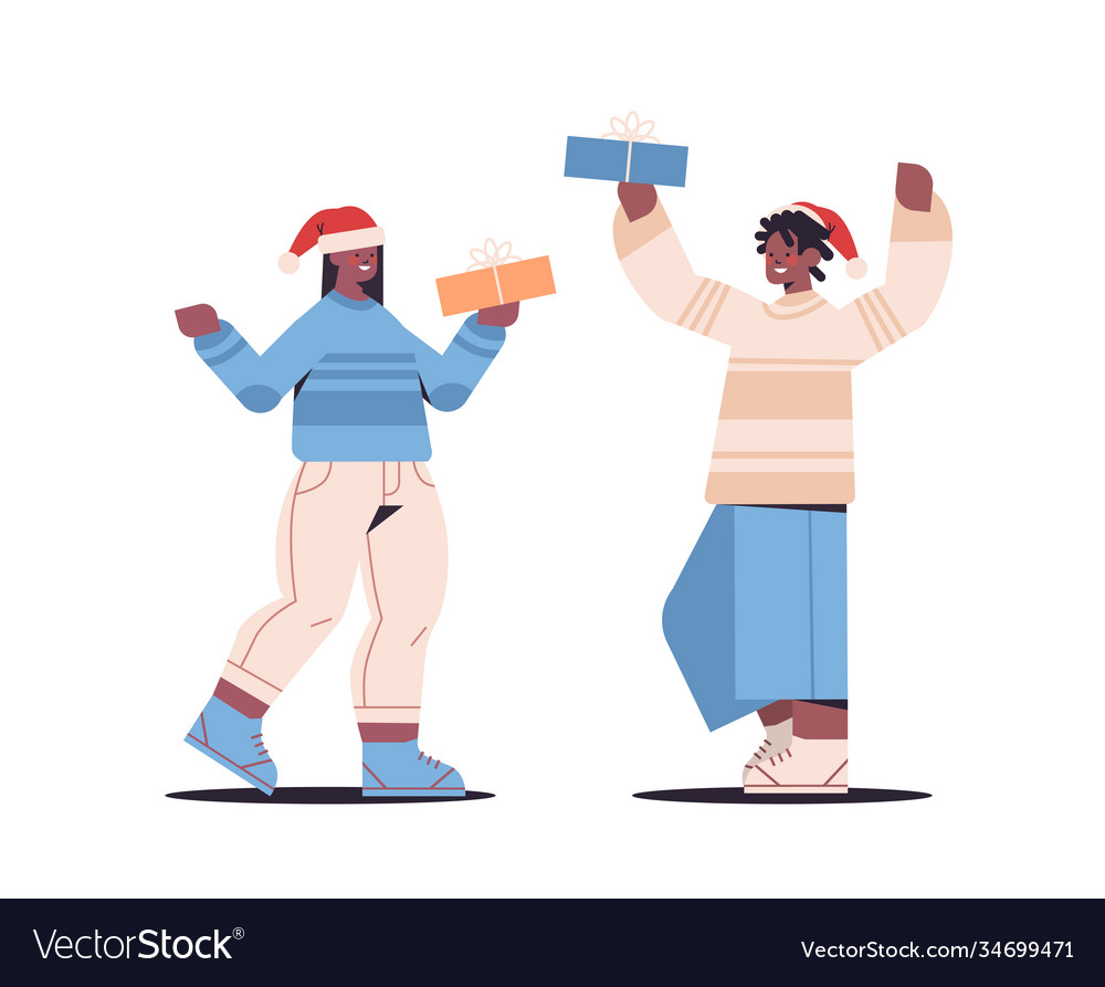 Couple in santa claus hats holding wrapped gift