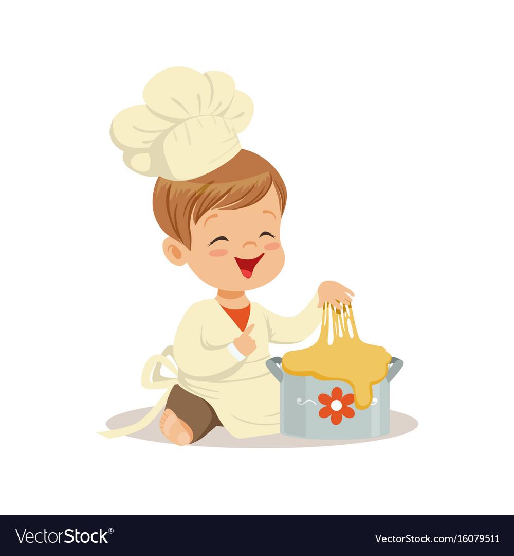 Cute smiling little boy chef kneading a dough