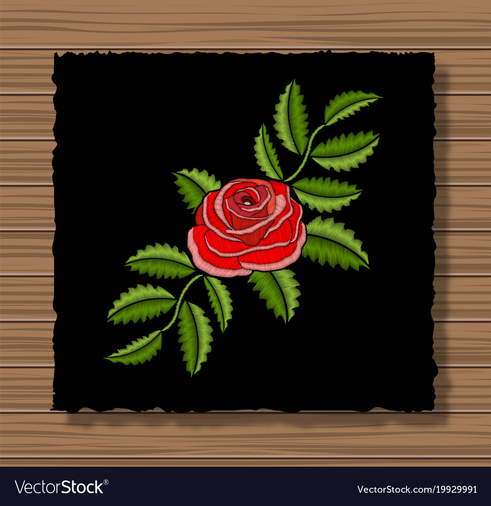 Embroidery rose on a dark flap cloth and wooden