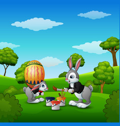 Happy easter bunnies painting easter eggs in the p vector