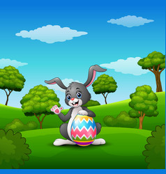Cartoon bunny waving hand with holding easter eggs vector