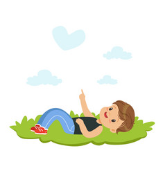 Sweet little boy lying on a grass and dreaming vector