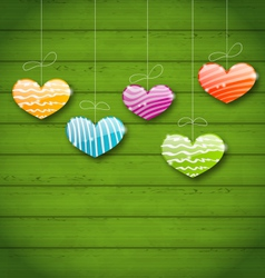 Colorful hearts hanging on green wooden texture vector image