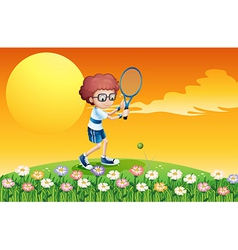 A boy playing tennis at the hill vector