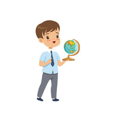 Cute boy standing with globe at geography lesson vector