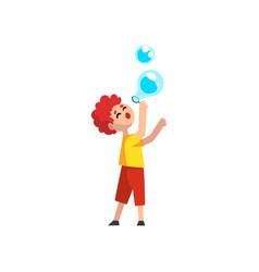 cute llttle redhead boy blowing soap bubbles vector image
