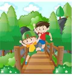two boys crossing the wooden bridge vector image