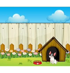 A puppy in front of the doghouse inside the fence vector