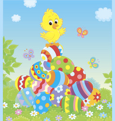 little easter chick on a pile of decorated eggs vector image