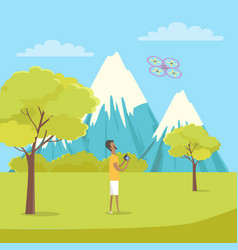 Boy playing with quadrocopter near mountains vector