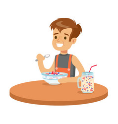 Cute smiling boy having breakfast in the kitchen vector