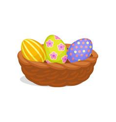 three painted easter eggs in brown wicker basket vector image