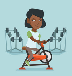 Young african woman riding stationary bicycle vector