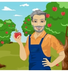 Mature farmer man holding an apple in orchard vector
