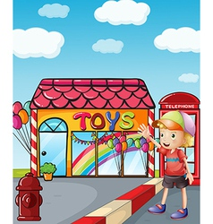 A boy wearing a hat waving outside the toy shop vector image vector image