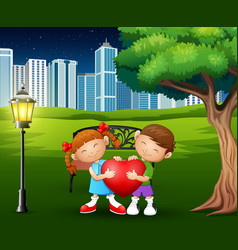 a couples holding red heart shape in the city park vector image