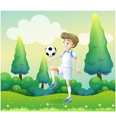 A hill with a young football player playing vector image vector image