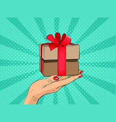 gift box in hand with red bow and ribbons vector image