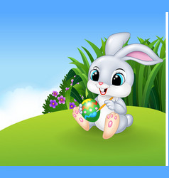 Cute Easter Bunny painting an egg on the Meadow vector