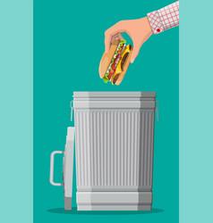 hand throwing away burger to trash bin vector image
