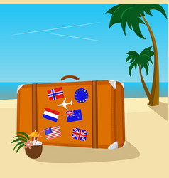 Vintage suitcase with flag stickers on beach vector