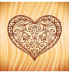 Brown ornate heart on wooden background vector