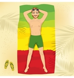 young man lying on a towel at the beach vector image