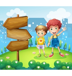The wooden arrow beside the two young boys vector image vector image