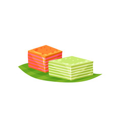 Kue lapis or small layered cakes on green leaf vector