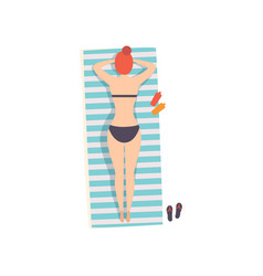 Young woman lying on her stomach on beach vector