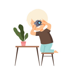 cute boy photographer holds camera in his hands vector image