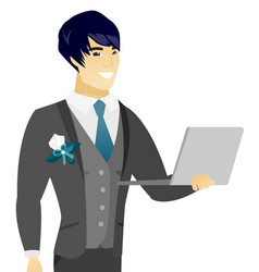 Young asian groom using a laptop vector