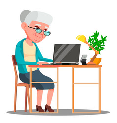 Elderly woman sitting at table and working with vector
