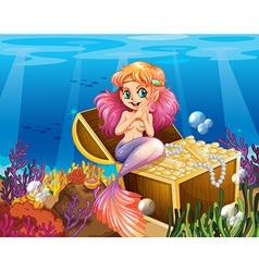 A mermaid under the sea beside the treasures vector image vector image