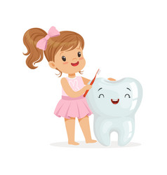 beautiful girl brushing a big smiling tooth with a vector image vector image