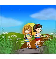 Two girls at the hilltop using their cellphones vector
