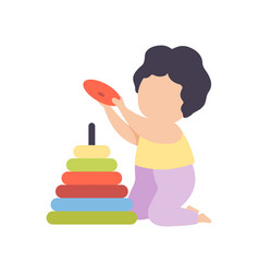 Cute little boy playing with colorful pyramid toy vector