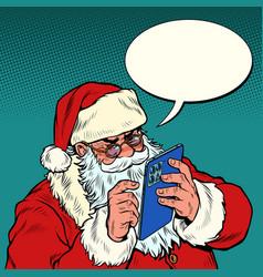 santa claus sends messages via mobile tablet vector image