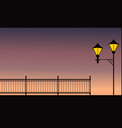 Silhouette of fence with street lamp at night vector