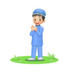 Cute muslim boy praying on grass vector