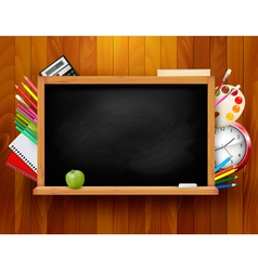 Blackboard with school supplies on wooden vector image