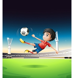 A boy in a red uniform at the soccer field vector image vector image