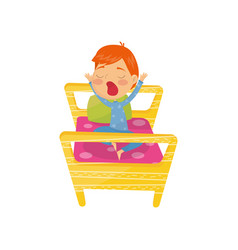 Cute red-haired boy waking up in bed and yawning vector