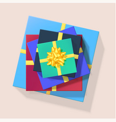 stack colored gift boxes with golden ribbons vector image