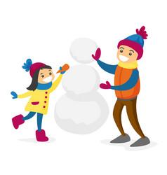 Caucasian white boy and girl building a snowman vector