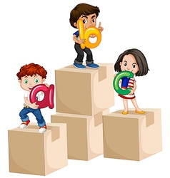 Children holding alphabets on boxes vector image